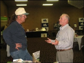 Bill Althouse, left, speaks with a convention attendee.